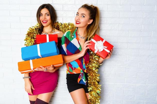 Schöne glückliche lächelnde beste freunde, die partygeschenke und -geschenke halten. trägt trendige kleidung und goldenes lametta Kostenlose Fotos