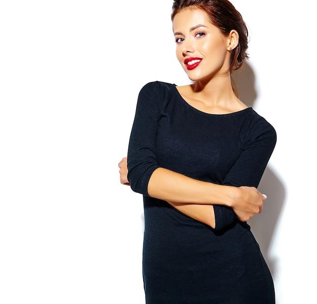 Schöne glückliche nette reizvolle brunettefrau im beiläufigen schwarzen kleid mit den roten lippen auf weißem hintergrund Kostenlose Fotos