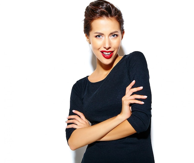 Schöne glückliche nette reizvolle brunettefrau im beiläufigen schwarzen kleid mit den roten lippen auf weißer wand Kostenlose Fotos