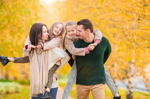 Schöne glückliche vierköpfige familie am herbsttag draußen Premium Fotos
