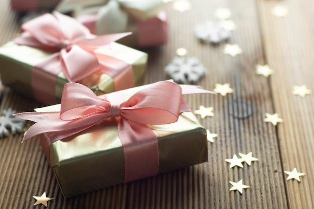 Schöne goldene geschenke weihnachten, party, geburtstagshintergrund. feiern sie shinny überraschungskästen copyspace hölzernen hintergrund Premium Fotos