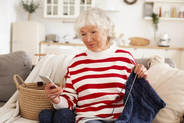 Schöne grauhaarige frau im ruhestand, die regnerischen tag zu hause sitzt, der auf couch sitzt und strickt, handy hält, textnachricht tippt. elegante großmutter messaging enkel online mit handy Kostenlose Fotos