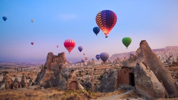 Schöne heißluftballons fliegen über kappadokien landschaft bei sonnenaufgang Premium Fotos