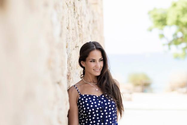 Schöne hispanische frau im blauen kleid, das auf wand beim weg schauen sich lehnt Premium Fotos