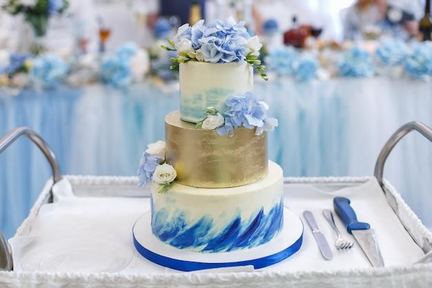 Schöne hochzeitstorte mit blumen auf einem tablett hautnah dekoriert. weiße und blaue abgestufte hochzeitstorte mit einer gabel und einem messer Premium Fotos