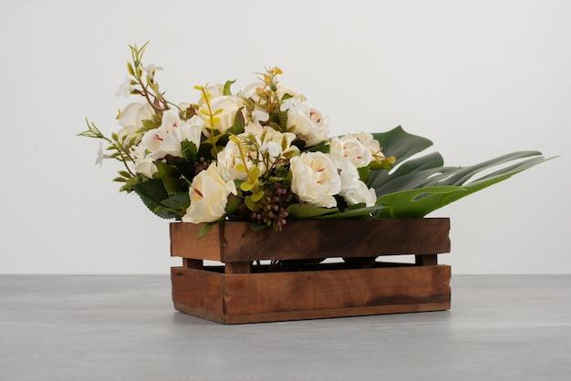 Schöne holzkiste der weißen rosen auf grauer oberfläche Kostenlose Fotos