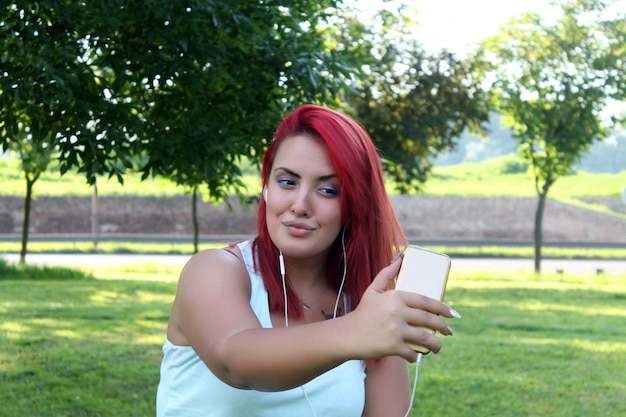 Schöne jugendfrau mit dem roten haar, das selbstporträt nimmt Premium Fotos