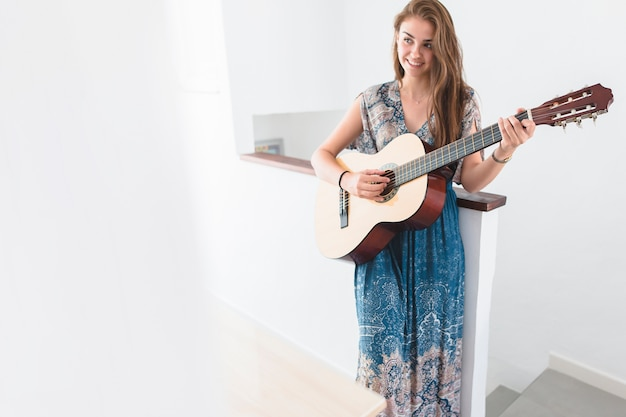 Schöne jugendliche, die zu hause gitarre spielt Kostenlose Fotos