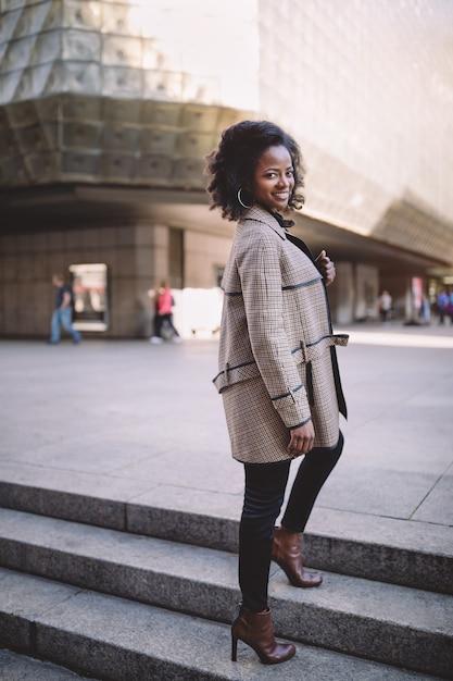Schöne junge afroamerikanerfrau mit afro und großen creolen in einem stilvollen mantel, lächelnd Premium Fotos