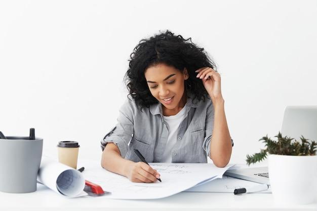 Schöne junge afroamerikanische frau architektin mit zeichnung des schwarzen lockigen haares mit stift Kostenlose Fotos