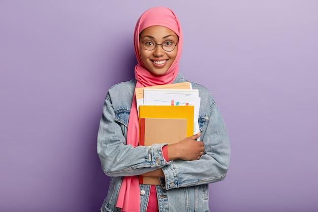 Schöne junge arabische frau mit dunkler haut, trägt transparente brille, hält papiere und notizblock, hat zahniges lächeln Kostenlose Fotos