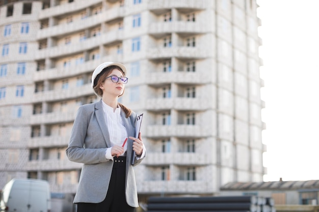 Schöne junge architektenfrau, die klemmbrett hält und weg schaut Kostenlose Fotos