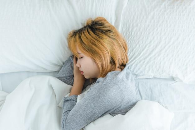 Schöne junge asiatin, die morgens im bett schläft Kostenlose Fotos
