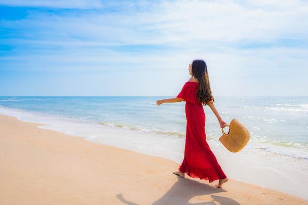 Schöne junge asiatische frau des porträts auf dem strand und dem meer Kostenlose Fotos