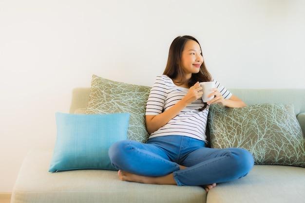 Schöne junge asiatische frau des porträts auf sofa mit kaffeetasse Kostenlose Fotos