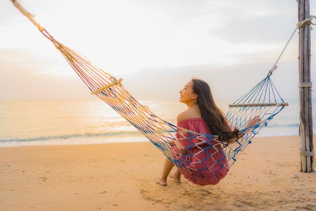 Schöne junge asiatische frau des porträts, die auf der hängematte mit glücklichem neary strandmeer und -oce des lächelns sitzt Kostenlose Fotos
