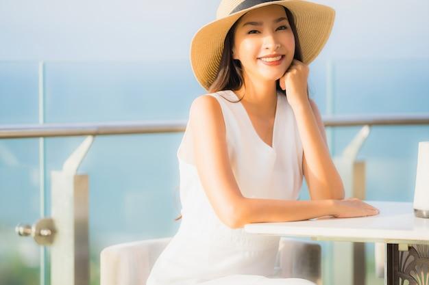 Schöne junge asiatische frau des porträts, die im restaurant sitzt Kostenlose Fotos