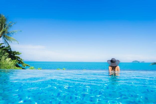 Schöne junge asiatische frau des porträts entspannen sich im luxusaußenpool im strandurlaubsort fast seeozean Kostenlose Fotos