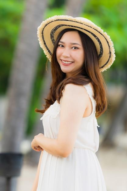 Schöne junge asiatische frau des porträts glücklich und lächeln auf dem strandmeer und -ozean Kostenlose Fotos