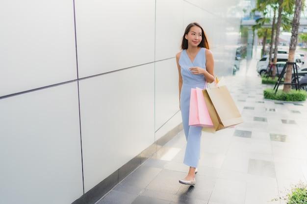 Schöne junge asiatische frau des porträts glücklich und lächeln mit einkaufstasche vom kaufhaus Kostenlose Fotos
