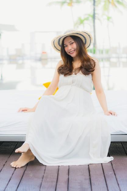 Schöne junge asiatische frau des porträts glücklich und lächeln mit reise in neary meer des hotels und strand Kostenlose Fotos