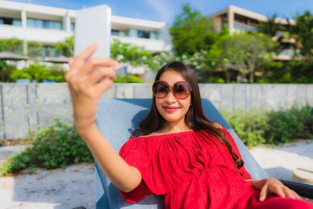 Schöne junge asiatische frau des porträts mit handy oder handy um swimmingpool am hotelerholungsort Kostenlose Fotos