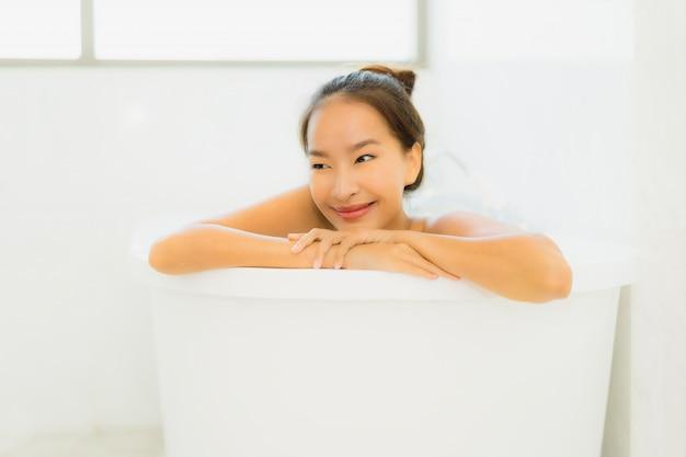 Schöne junge asiatische frau des portraits nehmen eine badewanne im badezimmer Kostenlose Fotos