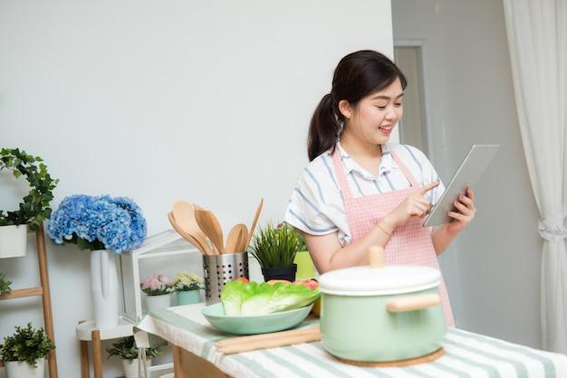 Schöne junge asiatische frau, die eine digitale tablette in der küche verwendet Premium Fotos