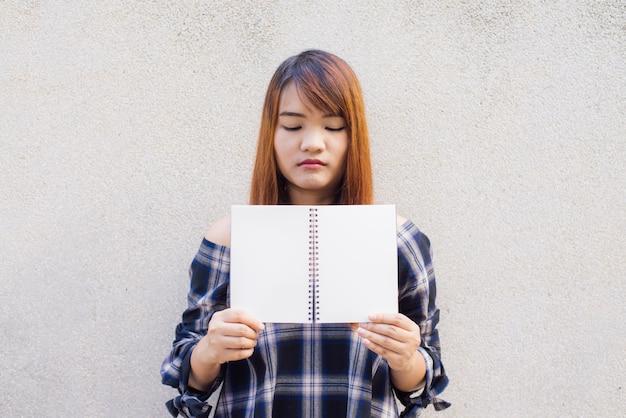Schöne junge asiatische frau, die hinter einem leeren spott sich herauf buch auf betonmauerhintergrund versteckt. vintage effekt stil bilder. Kostenlose Fotos