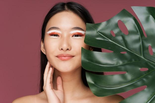 Schöne junge asiatische frau, die in den stilvollen kleidern aufwirft Premium Fotos