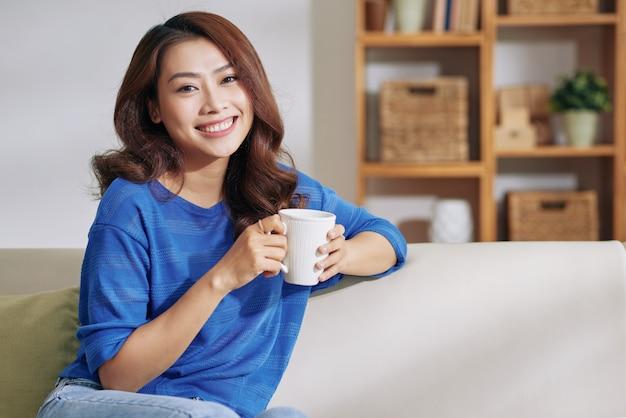 Schöne junge asiatische frau, die zu hause auf couch mit becher und dem lächeln sitzt Kostenlose Fotos