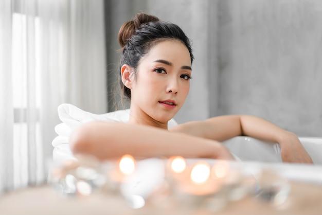 Schöne junge asiatische frau genießen das entspannen, ein bad mit blasenschaum in der badewanne am badezimmer nehmend Premium Fotos
