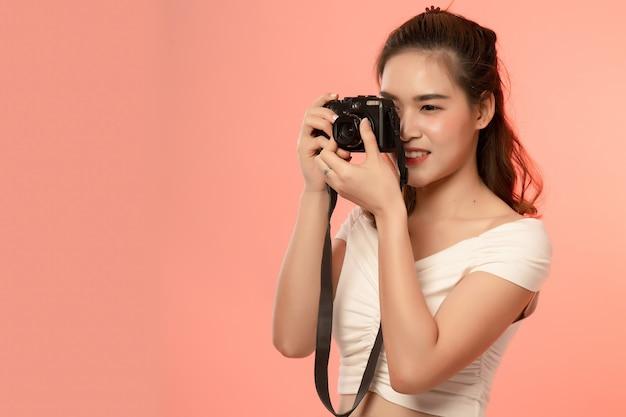 Schöne junge asiatische frau mit der kamera getrennt über rosa. weiblicher fotograf in der aktionsarbeit im studio. Premium Fotos