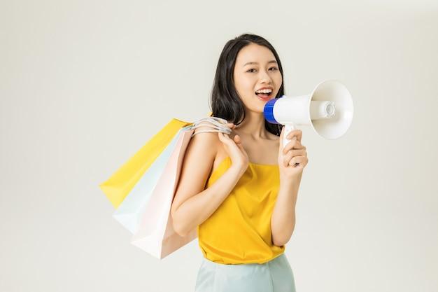 Schöne junge asiatische frau mit einkaufstüten und lautsprechern isoliert Premium Fotos