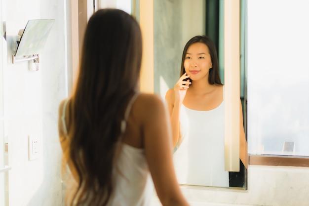 Schöne junge asiatische frau überprüft ihr gesicht im badezimmer Kostenlose Fotos