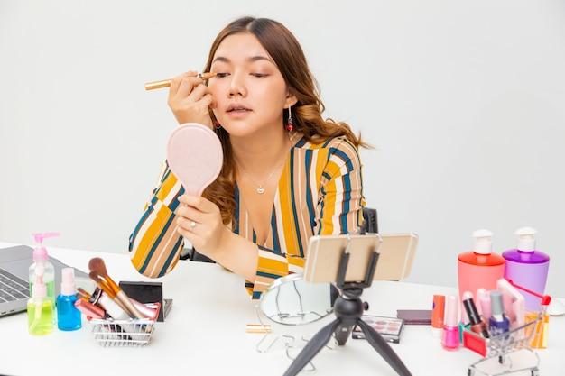 Schöne junge asiatische frau, vlogger, die ihr make-up und lidschatten aufsetzt, während sie schönheitsprodukte auf einem videoblog zu hause überprüft Premium Fotos
