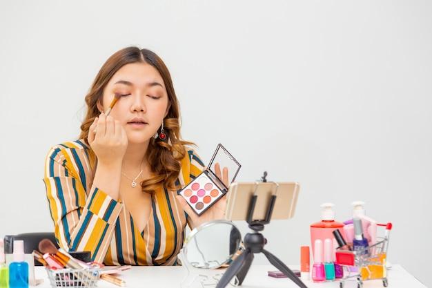 Schöne junge asiatische frau, vlogger, make-up und lidschatten beim überprüfen von schönheitsprodukten auf einem videoblog zu hause, raum für kopierraum Premium Fotos