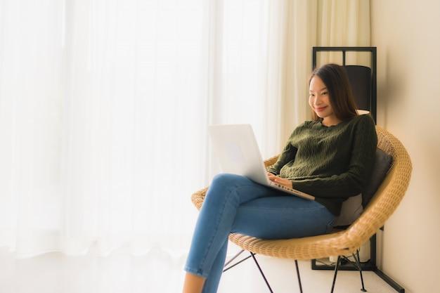 Schöne junge asiatische frauen des porträts, die computer oder laptop für das arbeiten und das sitzen auf sofastuhl verwenden Kostenlose Fotos