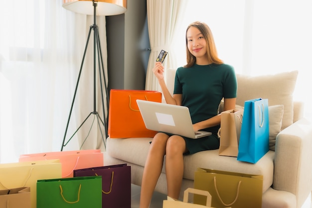 Schöne junge asiatische frauen des porträts, die computerlaptop mit kreditkarte für das on-line-einkaufen verwenden Kostenlose Fotos