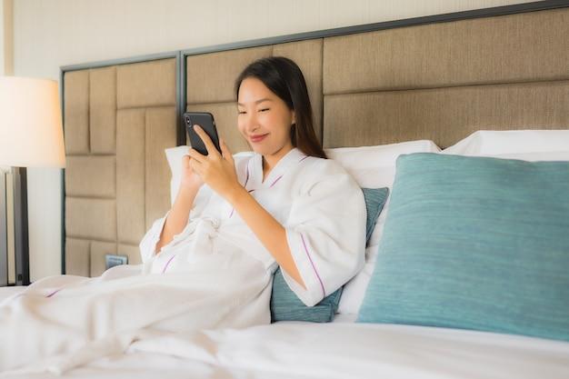 Schöne junge asiatische frauen des porträts, die mobile auf bett verwenden Kostenlose Fotos