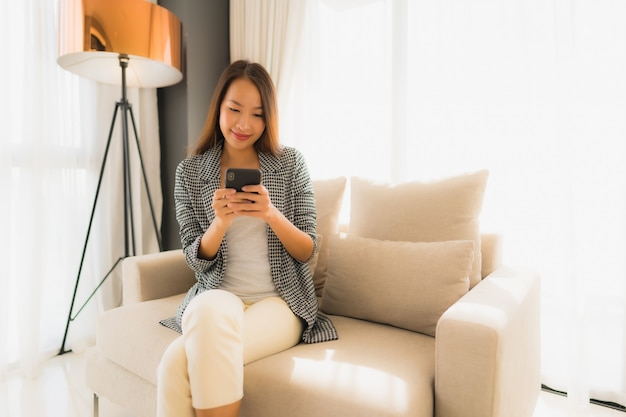 Schöne junge asiatische frauen des porträts, die unterhaltungshandy verwenden und auf sofastuhl sitzen Kostenlose Fotos