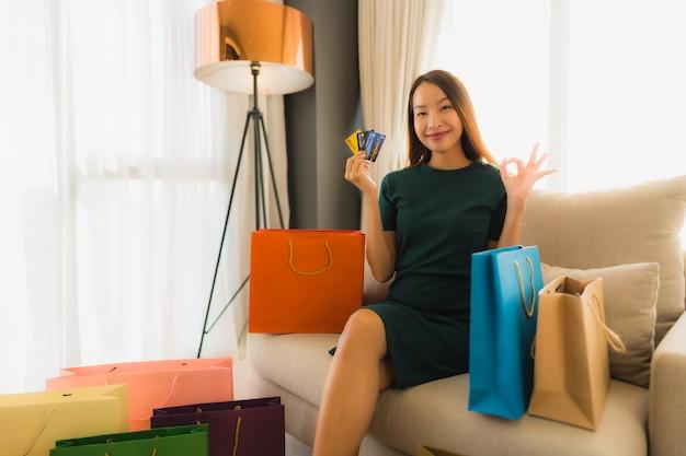 Schöne junge asiatische frauen des porträts mit kreditkarte für das on-line-einkaufen Kostenlose Fotos