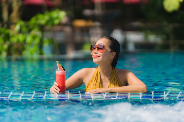Schöne junge asiatische frauenfreizeit des porträts entspannen sich lächeln mit wassermelonensaft um swimmingpool im hotelerholungsort Kostenlose Fotos