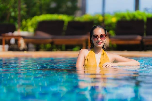 Schöne junge asiatische frauenfreizeit des porträts entspannen sich lächeln und glücklich um swimmingpool im hotelerholungsort Kostenlose Fotos