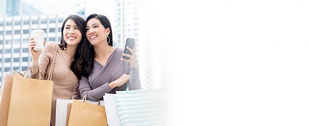 Schöne junge asiatische freundinnen, die das einkaufen in der stadt genießen Premium Fotos