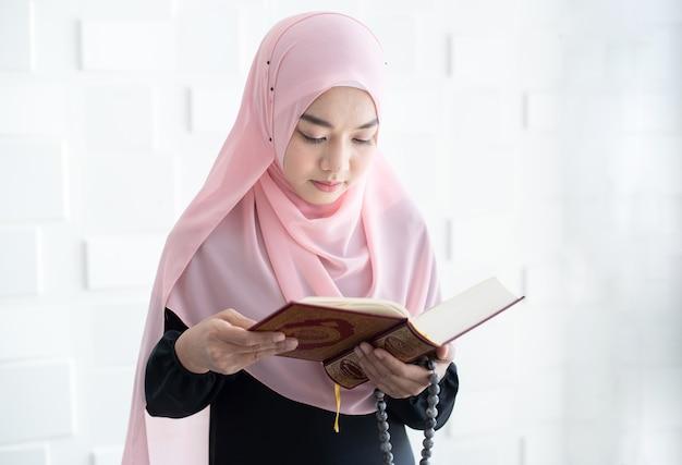 Schöne junge asiatische muslimische frau, die koran liest Premium Fotos