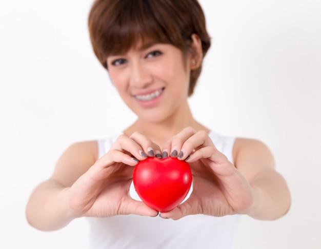Schöne junge asien-frau mit rotem herzen. isoliert auf weißem hintergrund Premium Fotos