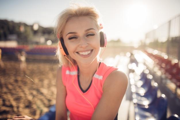 Schöne junge blonde frau im rosa bunten anzug, der musik auf kopfhörern am strand hört Premium Fotos