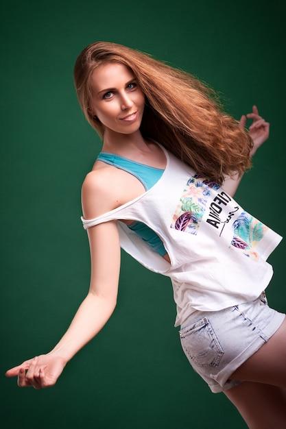 Schöne junge blonde frau in der weißen oberseite in den denimkurzen hosen lächelnd und aufwerfend Premium Fotos
