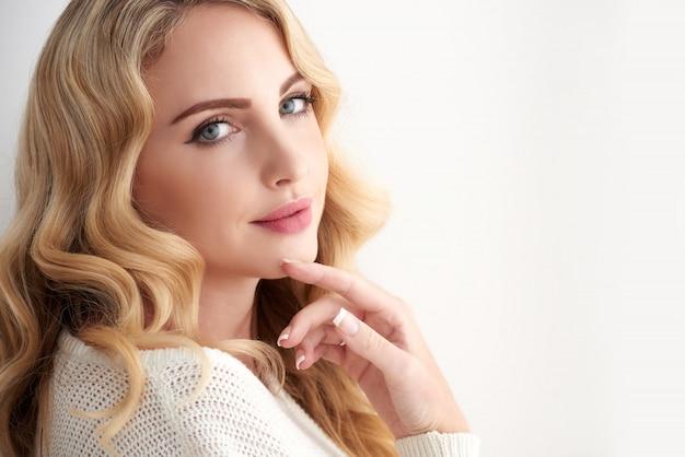 Schöne junge blonde kaukasische frau mit dem gewellten haar, das über ihrer schulter schaut Kostenlose Fotos